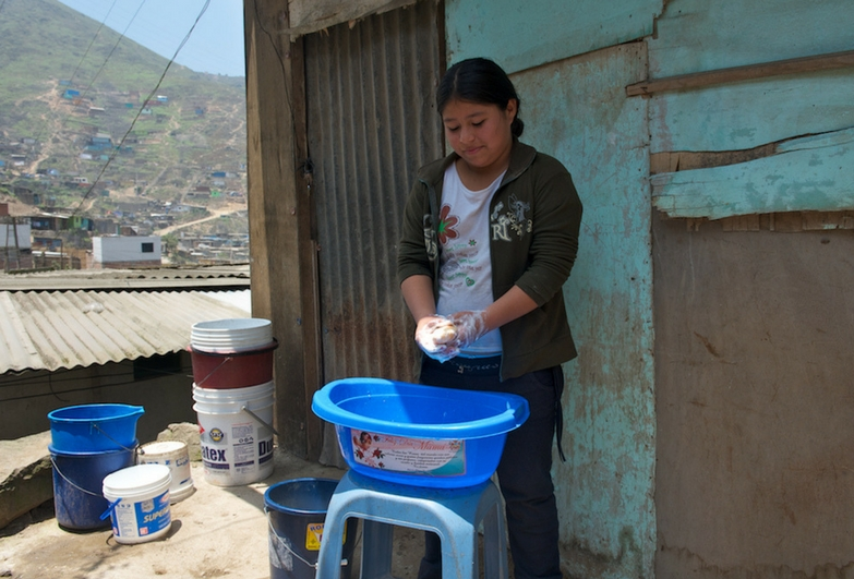 A child domestic worker washes up outdoors in Peru