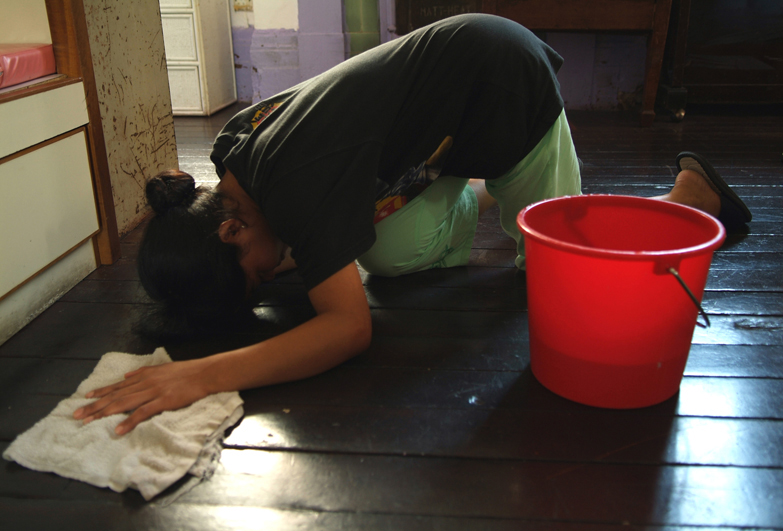 A domestic worker scrubs a floor