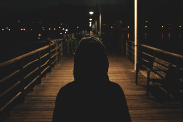hooded silhouette at night time