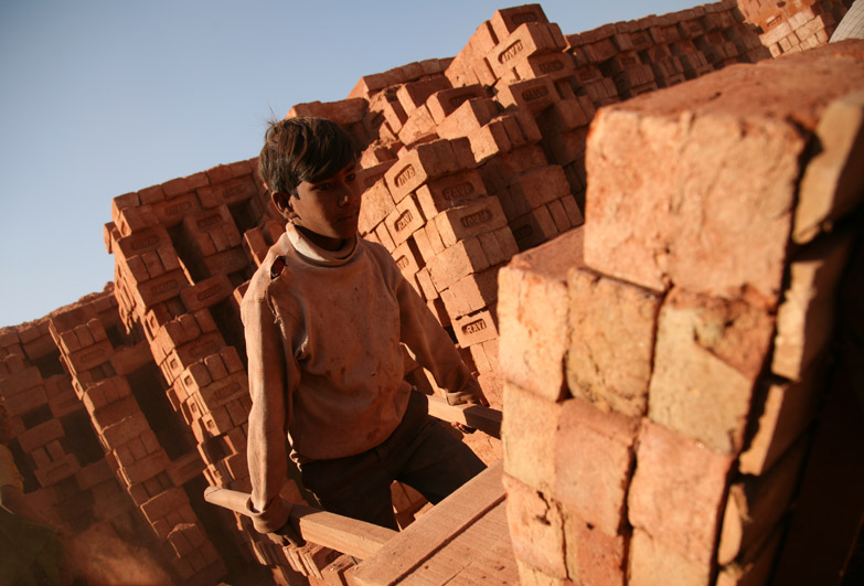 Young boy working in brick kiln in India