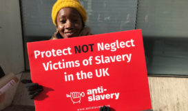 Holding sign that reads protect not neglect victims of slavery in UK