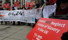 Holding sign protect not neglect victims of slavery in UK