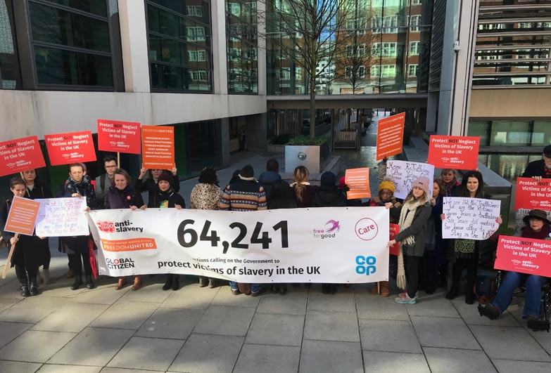 Survivors of slavery outside Home Office, their backs to the camera