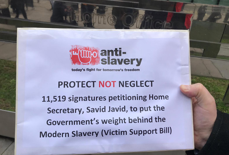 Holding protect not neglect sign outside UK Home Office