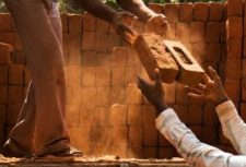 workers passing bricks