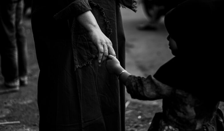Child holding the hand of a women in black and white